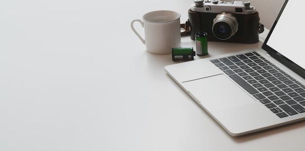 ラップトップコンピューターと白いテーブルテーブルの上のカメラで最小限のワークスペースのショットをトリミング