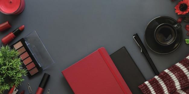暗い灰色の机の背景にコピースペースを持つ赤の高級フェミニンなワークスペースのトップビュー