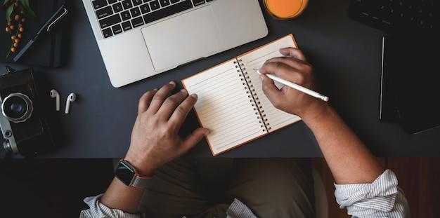 メモに彼のアイデアを書いている間彼のプロジェクトに取り組んでいる男のトップビュー