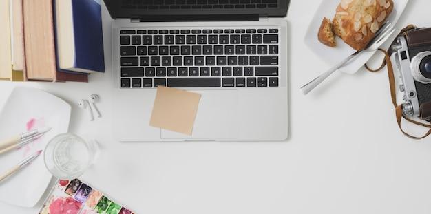 Верхний снимок уютного рабочего пространства с ноутбуком, канцелярскими товарами и инструментами для рисования