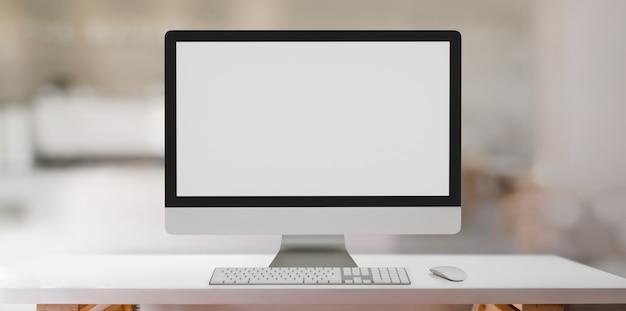 白いテーブルと背景をぼかした写真のデスクトップコンピューターのモックアップとモダンなワークスペース