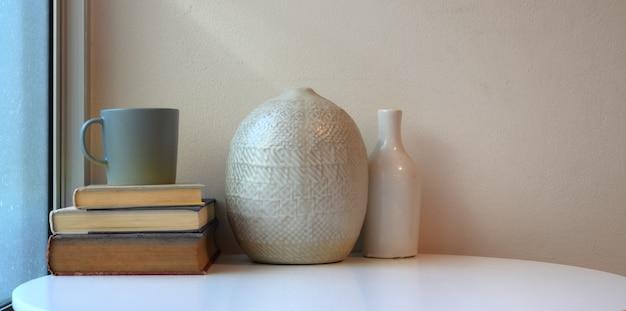 本とコーヒーカップの白いテーブルにセラミック花瓶と最小限のワークスペース
