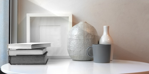 Керамические вазы и макет рамы на белом столе в минимальном рабочем пространстве