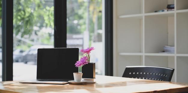 ピンクの花で快適なワークスペースで空白の画面のラップトップコンピューターを開く