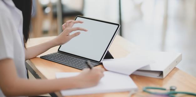 若い女性医師がデジタルタブレットで患者のカルテを調べるとドキュメントに書き留める