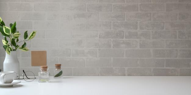 Минимальное рабочее пространство с копией пространства и канцелярских товаров на белом столе и серой кирпичной стене