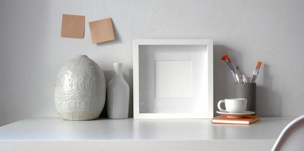 Минимальное рабочее пространство с рамой и копией пространства с керамической вазой
