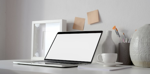 Минимальное рабочее пространство с открытым пустым экраном ноутбука и рамка на белом столе