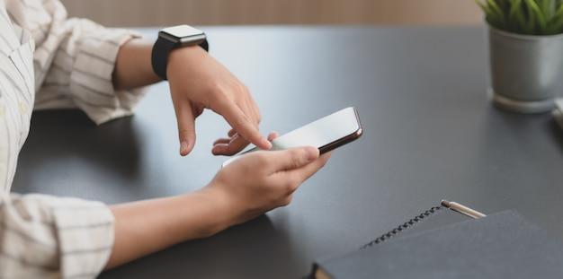 空白の画面のスマートフォンに触れる若いプロの実業家のクローズアップビュー