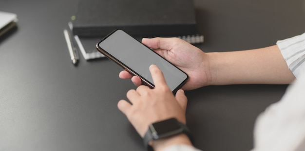空白の画面のスマートフォンを保持している若いプロの実業家のクローズアップビュー