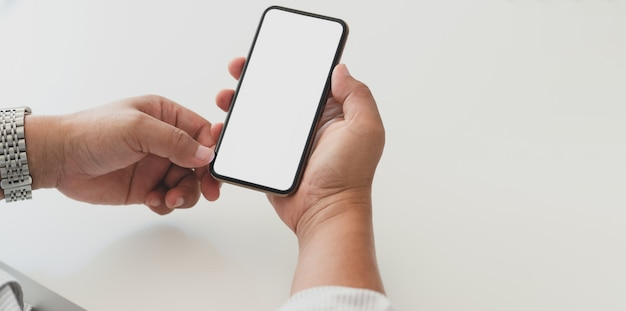 空白の画面のスマートフォンを保持しているプロのビジネスマンのクローズアップビュー