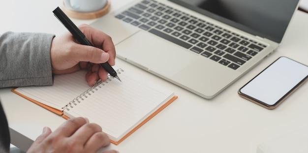 ノートにアイデアを書きながら彼のプロジェクトに取り組んでいるビジネスマンのショットをトリミング