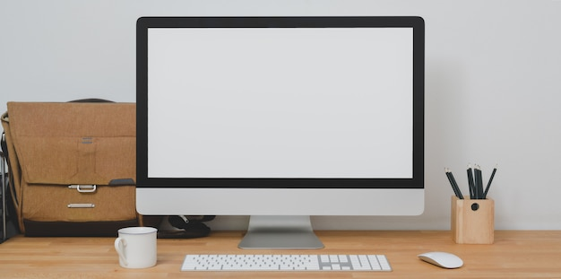 事務用品とメールバッグを備えたモダンなホームオフィスルームのデスクトップコンピューターのモックアップ