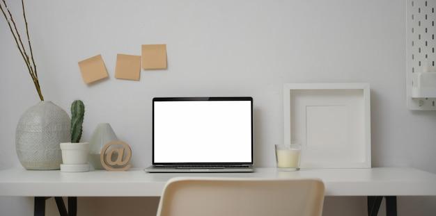 フレームと装飾のモックアップを備えた空白画面のラップトップコンピューターを備えた最小限のワークスペース