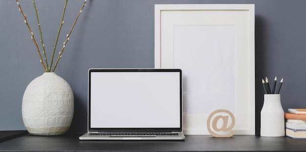 開いた空白画面のラップトップコンピューターとモックアップフレームを備えた最小限のワークスペース