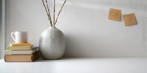 Минимальное рабочее пространство с копией пространства и керамические украшения вазы на белом столе и белой стене