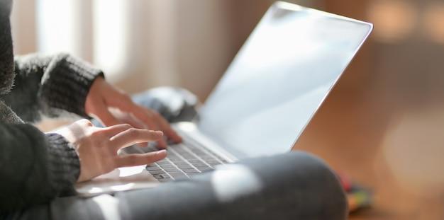 ラップトップコンピューターで彼女のプロジェクトに取り組んでいる若い女性フリーランサーのクローズアップビュー