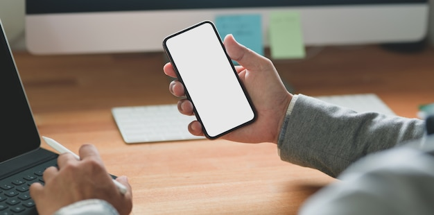 彼のプロジェクトに取り組んでいる間空白の画面のスマートフォンを保持している青年実業家