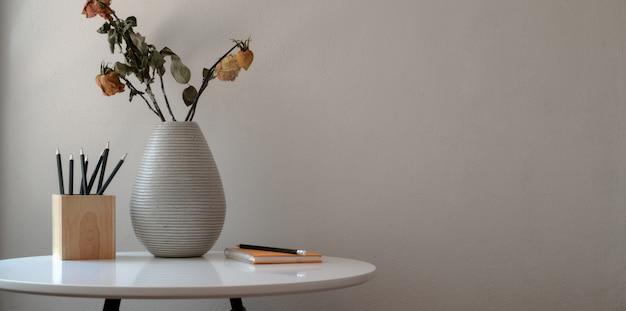 白いテーブルに乾燥したバラの花瓶と事務用品と最小限のワークスペース