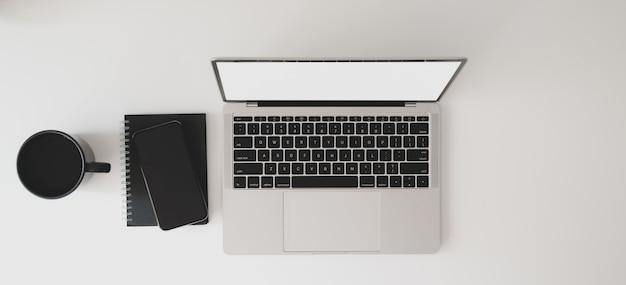 ラップトップコンピューター、ノートブック、コーヒーカップとモダンなワークスペースの平面図