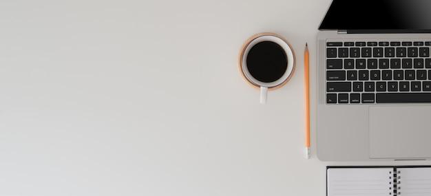 ラップトップコンピューター、事務用品、コーヒーカップとモダンなワークスペースのトップビュー
