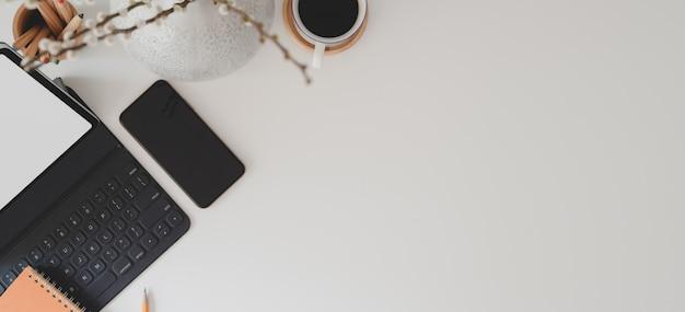 デジタルタブレット、キーボード、スマートフォン、コーヒーカップとモダンなワークスペースの平面図
