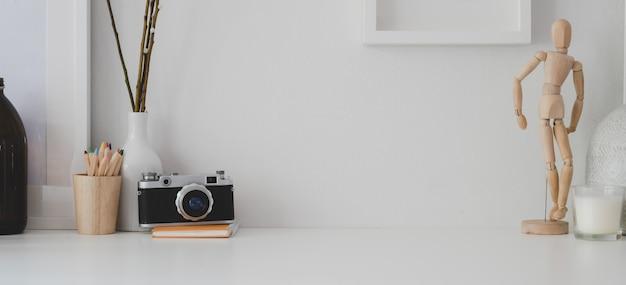 白い机と白い壁にコピースペース、カメラ、オフィス用品を備えた最小限のワークスペース