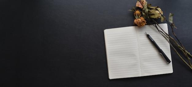 開いているノートブック、ペン、黒い革の机の上の乾燥したバラと暗い空のワークスペース