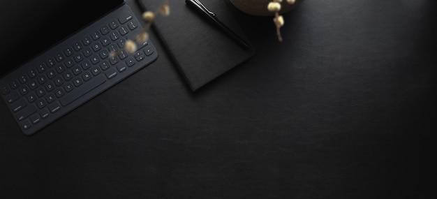 黒い革の机の上のタブレットとオフィス用品と暗いモダンなワークスペースの平面図