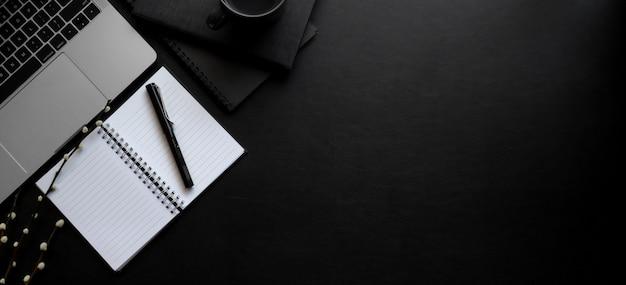 Накладные выстрел из темного современного рабочего пространства с ноутбуком и открытой записной книжкой