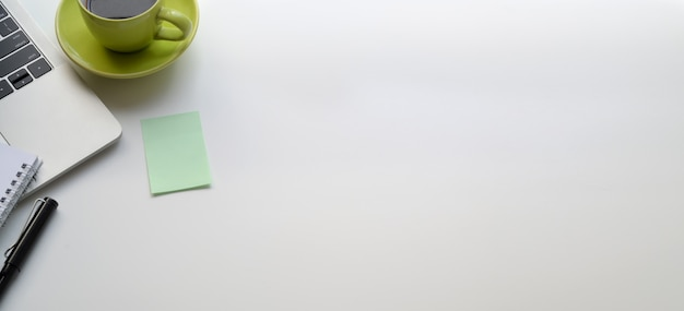白いテーブルの上のラップトップコンピューターと緑のコーヒーカップと現代の職場のトップビュー