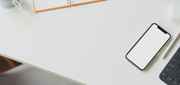 Сверху снимок минимального рабочего пространства с макетом смартфона с канцелярскими товарами