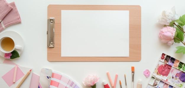 Накладные выстрел из розового женского рабочего пространства художника с эскиза бумаги и инструментов рисования