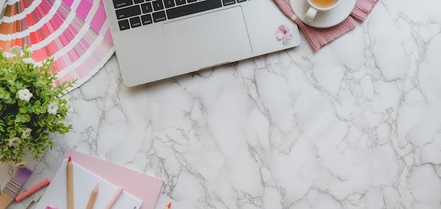 Накладные выстрел из розового женского дизайнерского рабочего пространства с ноутбуком и инструменты рисования на мраморном столе