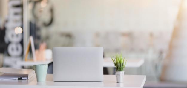 Обрезанный снимок удобного рабочего места с ноутбуком и канцелярских принадлежностей на фоне солнечного света