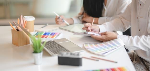 グラフィックデザイナーのチームのアイデアを現代のオフィスで一緒に交換するショットをトリミング