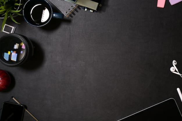タブレット、レンズ、デザイナーガジェットを使ったクリエイティブなダークレザーデスク