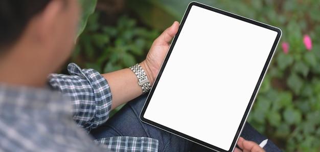 庭の背景を持つ空白の画面のタブレットで彼のプロジェクトに取り組んでいる実業家のショットをトリミング