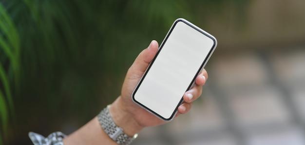 ぼやけた庭の背景を持つ空白の画面のスマートフォンを保持しているプロのビジネスマンのショットをトリミング
