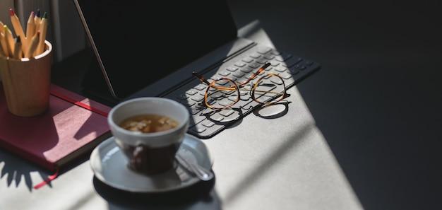 コピースペースを持つ暗い灰色のテーブルにタブレットとオフィス用品と現代の職場のクローズアップビュー