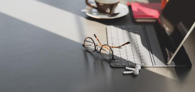 コピースペースと暗い灰色のテーブルにデジタルタブレットとオフィス用品と近代的なオフィスルーム