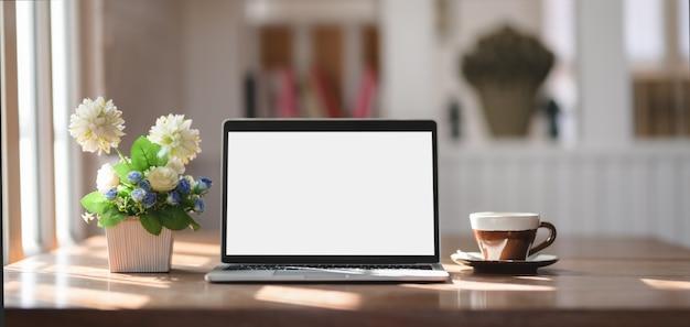 木製のテーブルにラップトップコンピューター、コーヒーカップ、ツリーポットのモックアップで快適な職場