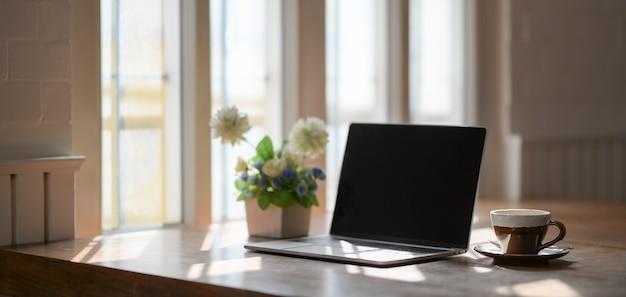 ラップトップコンピューター、コーヒーカップ、木製のテーブルの上の木の鍋で快適な職場