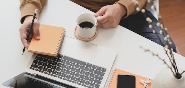 Обрезанный снимок молодого человека, работающего на своем удобном рабочем месте, попивая кофе
