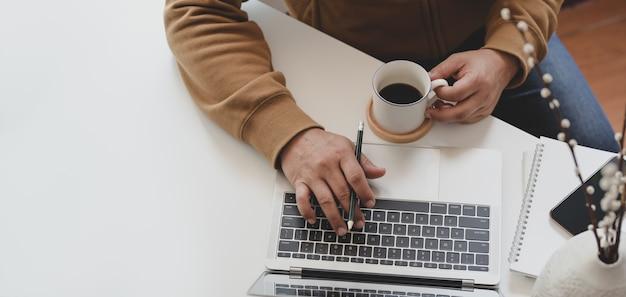 Обрезанный снимок молодого человека, набрав на ноутбуке и пить кофе