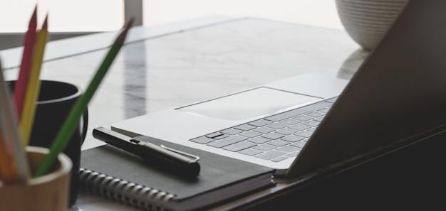 Крупным планом вид удобного рабочего места с ноутбуком и канцелярскими товарами