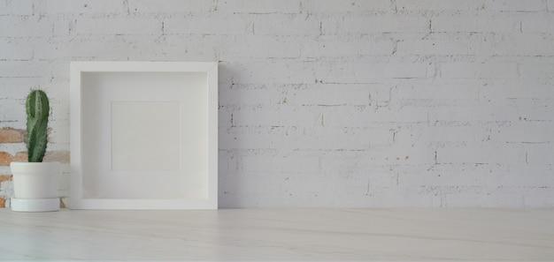 白いテーブルと白いレンガの壁に最小限の事務室でサボテンポットとフレームをモックアップします。