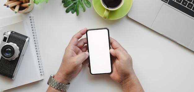 Вид сверху профессиональный мужской дизайнер, держа смартфон пустой экран на своем рабочем месте