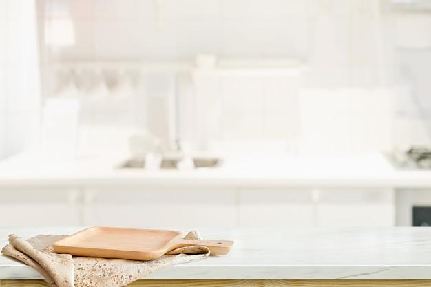 Деревянная тарелка на белом столе на фоне кухни