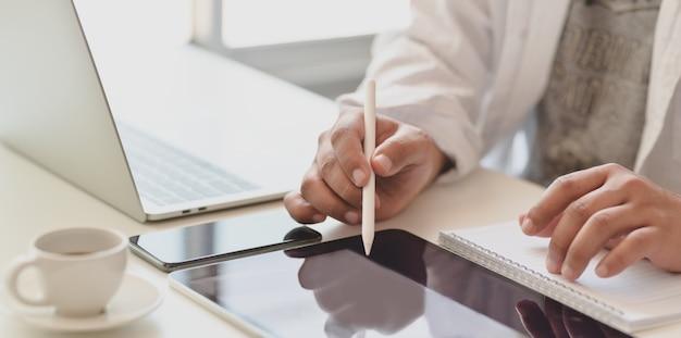 Обрезанный снимок молодого мужчины, пишущего фрилансером на планшете во время работы над его проектом